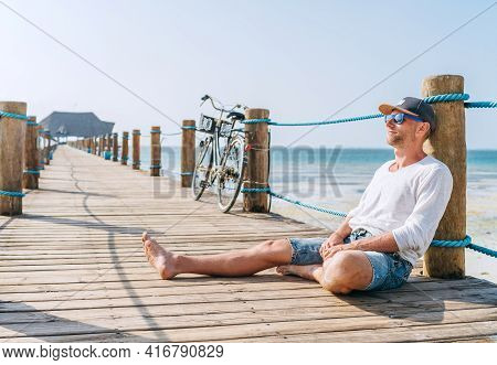 Portrait Of A Happy Smiling Man Dressed In Light Summer Clothes And Sunglasses Sitting And Enjoying