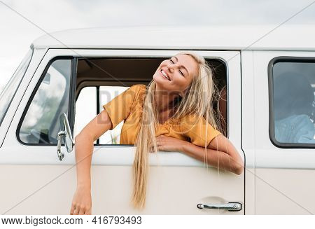 Happy Blond Woman With Closed Eyes Sitting On A Driver Seat Enjoying A Road Trip