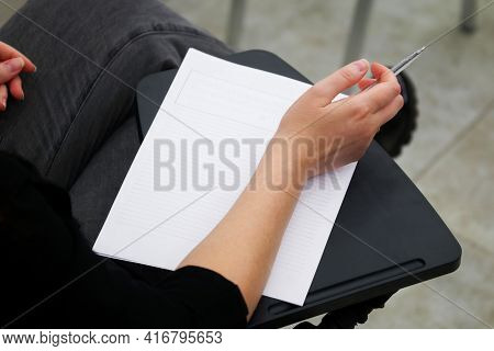 A Girl Is Preparing To Fill Out A Blank Form, Write An Essay Or Dictation, Sitting On A School Chair