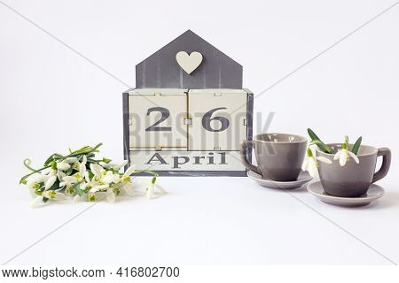 Calendar For April 26: Cubes With The Number 26, The Name Of The Month In English, Two Gray Coffee C