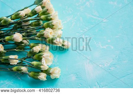 Small Bouquet Of White Carnations In On A Blue Background, Copy Space. Symbol Of Love, White, Yellow
