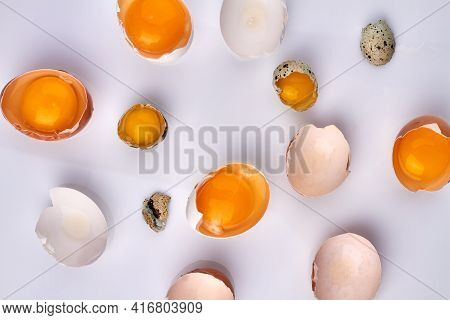 Mixed Broken Quail And Chicken Eggs With Yolk On White Background.