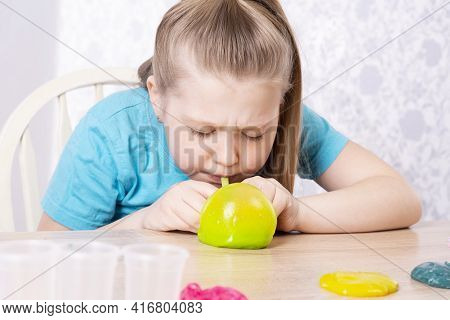 A Blonde Child Inflates A Bottle Of Yellow Slime. Play A Slime Toy. Making Slime At Home