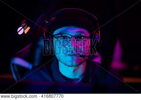 Close-up Portrait Of A Young Gamer At The Computer. A Gaming Headset With Headphones On The Head. Ne