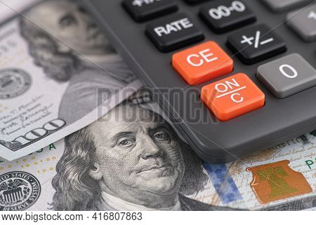 One Hundred Dollar Bills And Calculator. Close Up.