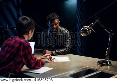 A Young Artist Owner Of A Tattoo Parlor Draws A Sketch On Paper For A Black Client Who Wants To Choo