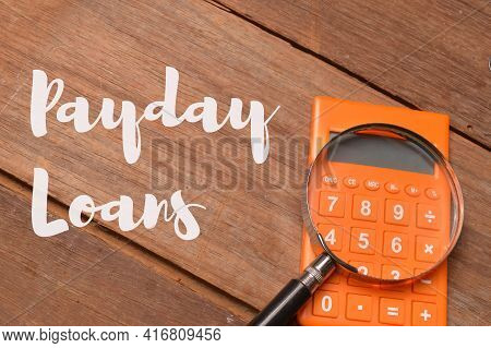 Top View Of Magnifying Glass And Calculator Over Wooden Background Written With Payday Loans. Busine