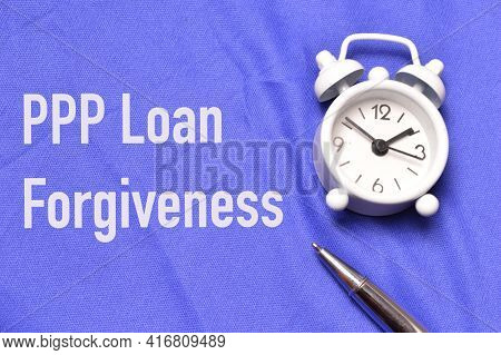 Top View Of Clock, Pen Over Blue Background Written With Ppp Loan Forgiveness.
