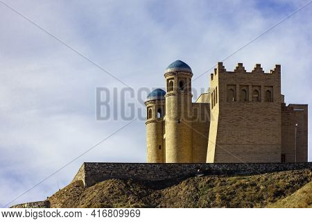 An Ancient Fortress On A Hillside Against The Sky In The Mountains. Old Historical Defensive Structu