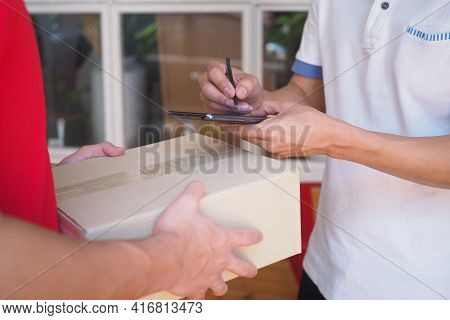 The Sender Holds The Box, Prepares To Send The Order And Sign The Recipient On The Smartphone.