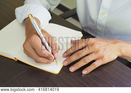 A Male Employee Is Taking Notes Of His Work Into The Book. Writing Notes