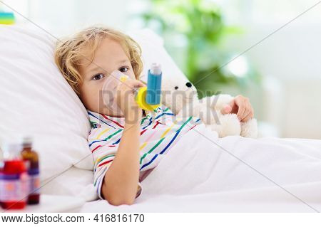 Sick Little Boy With Asthma Medicine. Ill Child Lying In Bed. Unwell Kid With Chamber Inhaler For Co