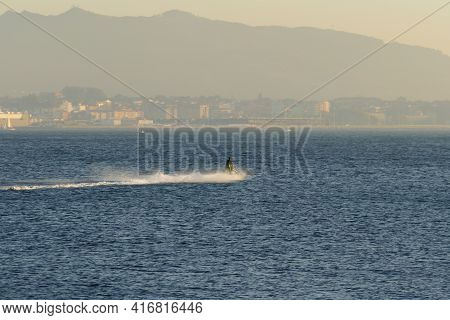 Unrecognizable Person Rides A Jet Ski Through The Sea With Fog In The City Of Vigo In The Background