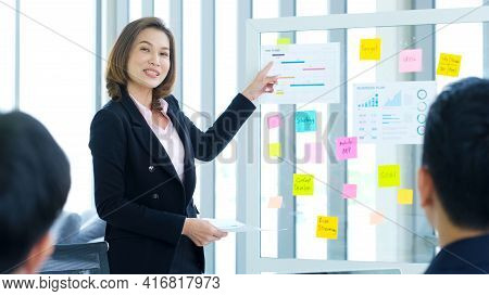 Businesswoman Presenting Business Plan Information To Team At Office Meeting, Asian Leader Man Expla