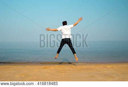 Jump To Ocean Beach For Holiday Free. Backyard Of Man Jumping Action From The Beach For Relax To Nat