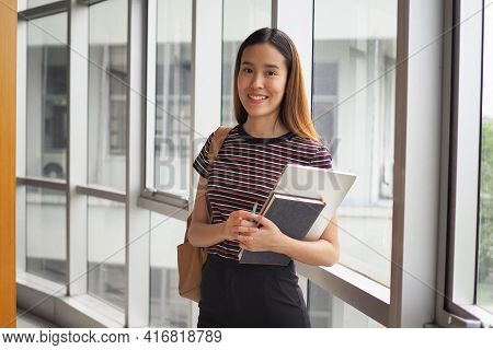 Beautiful Female Student With A Book In High School Or University