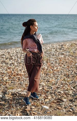 Caucasian Girl With Dreadlocks On Stone Shore Closed Her Eyes Because Of Bright Sun. Warm Summer Pho
