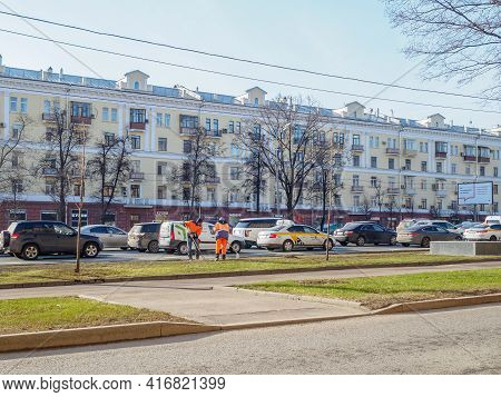 Moscow. Russia. 06 April 2021. Orange-uniformed Janitors Sweeping The Lawn Along A Road On A City St