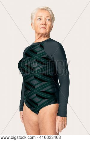 Mature woman in surfing swimsuit summer apparel on beige background