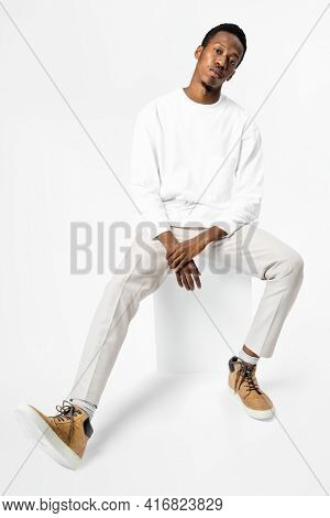 African American man in white sweater sitting on a chair full body