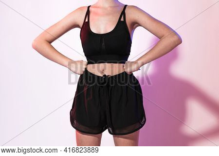 Sporty woman in sports bra and sweatpants for activewear photoshoot