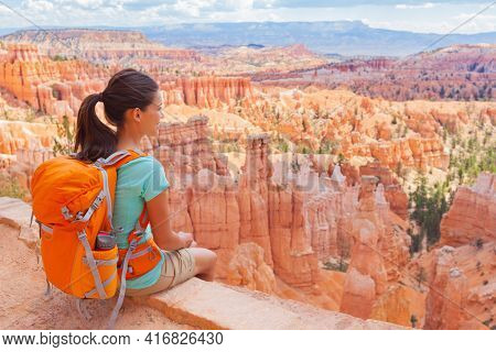 USA Hiker woman in Bryce Canyon hiking relaxing looking at view during hike wearing backpack on summer travel. Bryce Canyon National Park landscape, Utah, United States.