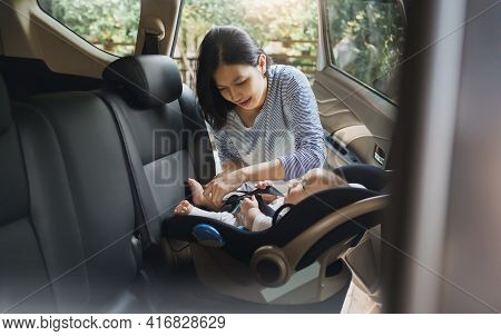 Asian Young Mother Putting Her Baby Son Into Car Seat And Fasten Seat Belts In The Car For Safety In