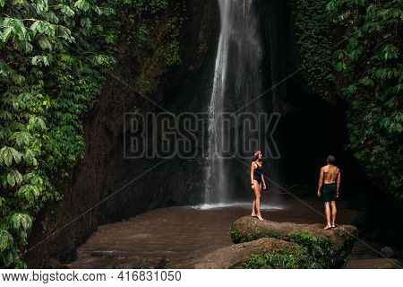 Couple At A Tropical Waterfall. The Couple Travels To The Island Of Bali In Indonesia. A Woman And A