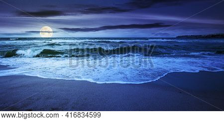 Sea Tide On A Cloudy Sunrise. Green Waves Crashing Golden Sandy Beach In Full Moon Light. Storm Weat