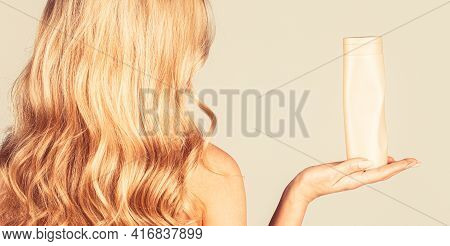 Woman Holding Shampoo Bottle. Beautiful Blonde Girl With A Bottle Of Shampoos In Hands. Girl With Sh