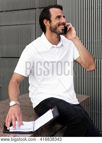 White polo shirt man talking on the phone menswear apparel fashion