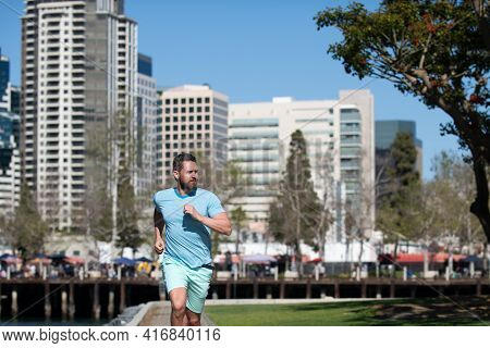 Full Length Of Healthy Man Running And Sprinting Outdoors. Male Runner