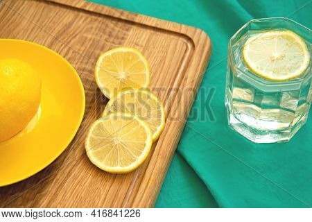 Lemon And Slices Of Lemon On Wooden Cutting Board And Glass Of Water On Background Of Turquoise Fabr