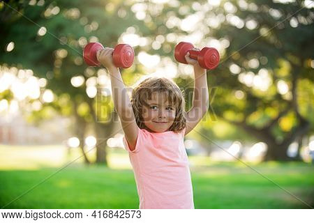 Kids Sporty Lifestyle. Boy Workout In Park. Kid Sport. Child Exercising With Dumbbells. Sporty Child