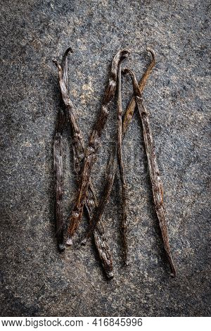 Vanilla pods. Sticks of vanilla on black table. Top view.