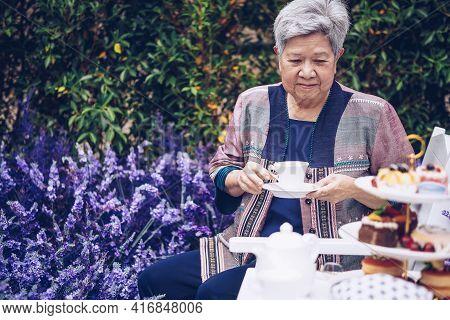 Asian Old Elderly Elder Woman Drinking Coffee Tea In Lavender Flower Garden. Senior Leisure Lifestyl