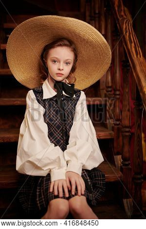 Beautiful girl in elegant classic school uniform and wide-brimmed straw hat sits on the steps in a classic vintage interior. British style. Kid's fashion.