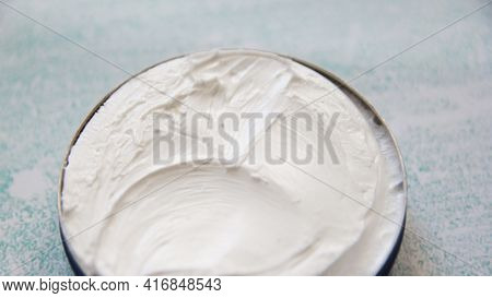 Jar With Body Cream On Blue Background. Open White Jar With White Face Cream On A Background Of Smea
