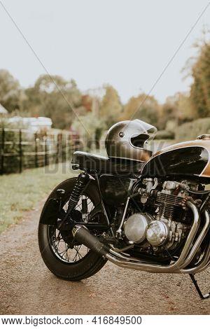 Vintage motorbike and helmet parked in countryside