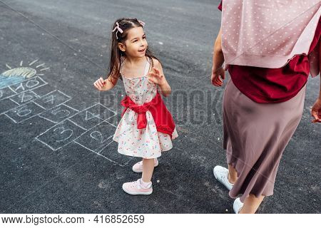 Outdoor Image Of A Little Girl Playing Hopscotch With Her Mother On Playground Outdoors. Child Plays