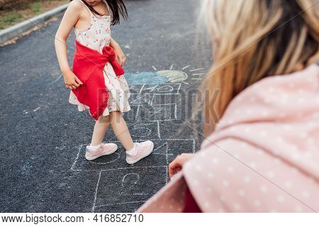 Cropped Image Of A Little Girl Playing Hopscotch With Her Mother On Playground Outdoors. A Child Pla