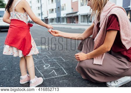 A Little Girl Drawing With Colorful Chalks On The Playground Together With Her Mum. Child Playing Wi