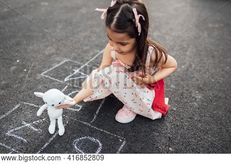 Image Of A Cute Little Girl Playing With Her Favorite Toy, Hopscotch On The Playground. Child Playin