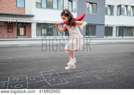 Full View Of Little Girl Playing Hopscotch With Her Mother On Playground Outdoors. Horizontal Image