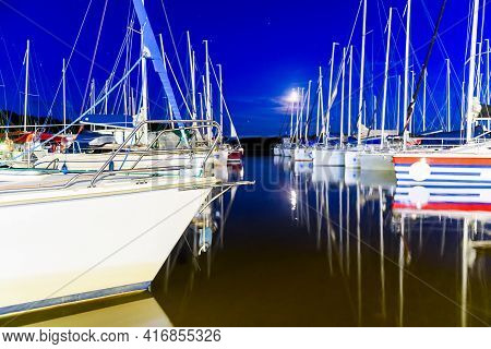 Yachts Moored In A Harbor At Night. Sailboats In The Dock. Summer Vacations, Cruise, Recreation, Spo
