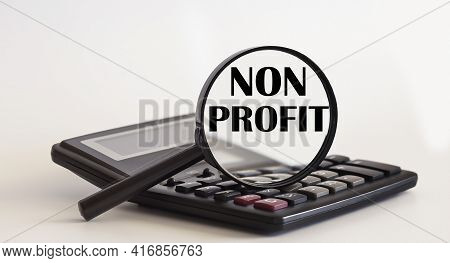 Focused On The Non Profit Concept. Magnifier Glass With Text On Calculator. Business Concept