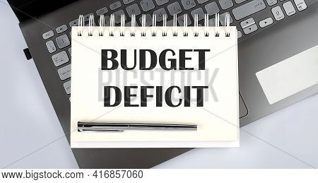 Budget Deficit - Top View Notebook Writing On Laptop