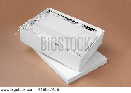 Top View Mockup A White Open Box With Clothes In A Clean Blank White Tissue Paper And Shredded Paper