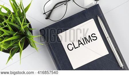 Stickers On Notebook Text Claims With Pen And Glasses On The White Background