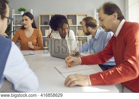 Group Of Diverse Business People Discussing Their Projects Sitting At Office Table Together